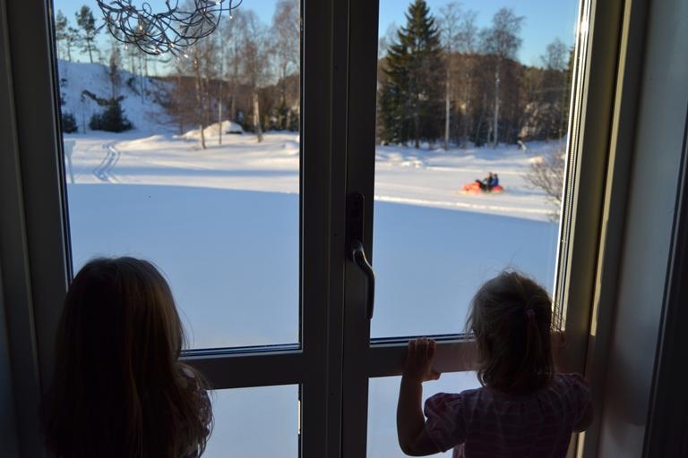 Här står Tyra och Betty (och katten Hjalmar men han syns inte på bild) och tittar på när storebror Gustav och hans kompis Krille åker skoter nere på åkern. :)
