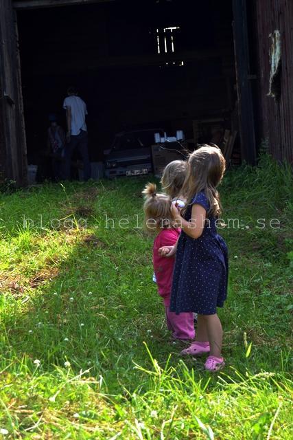 Söta systrar tre står på rad hand i hand och tittar på när storebor och kusinen jobbar.