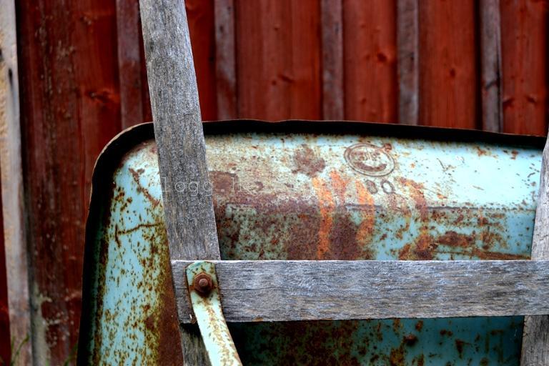 En gammal skottkärra mot en gammal faluröd byggnad