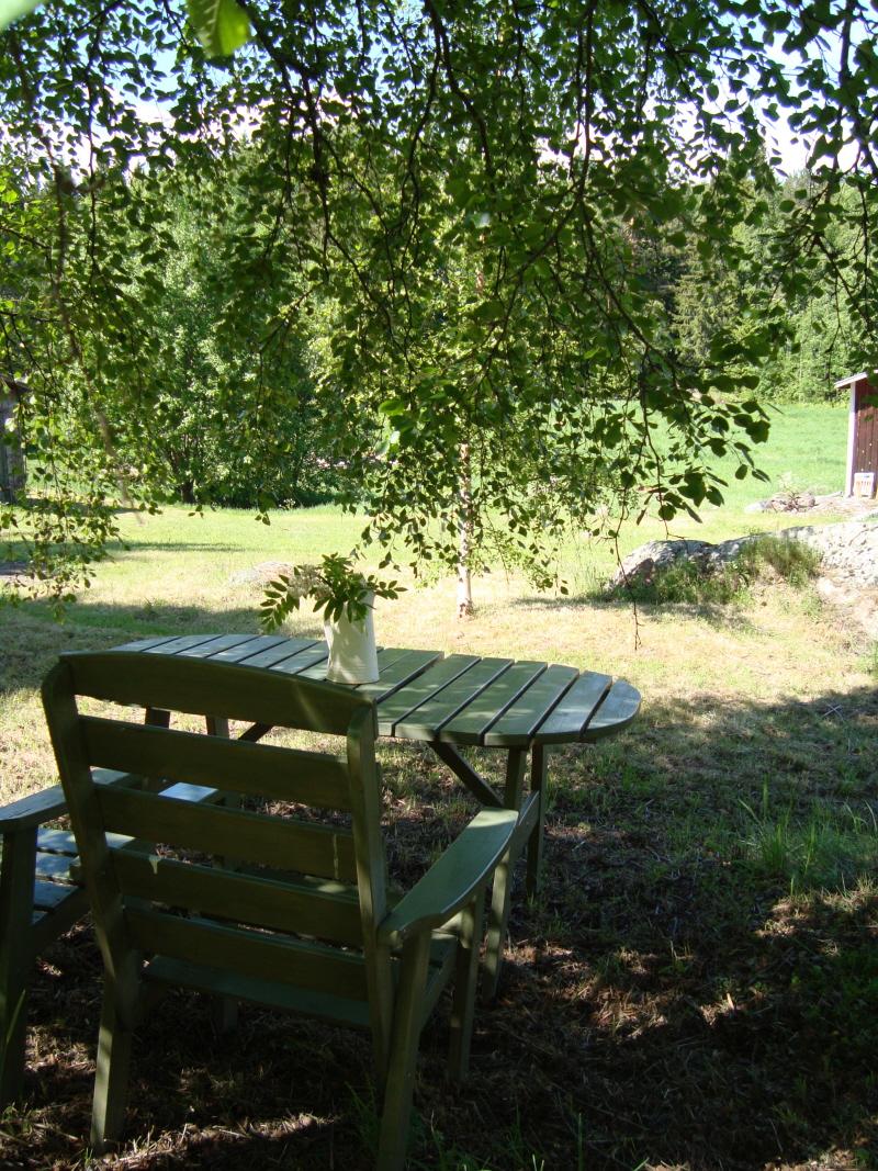 De gröna trädgårdsmöblerna försvinner nästan under björken av allt grönt. Byggnaden som skymtas till höger är Hönshuset.
