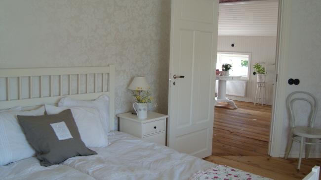 Vårt sovrum, allrummet skymtar