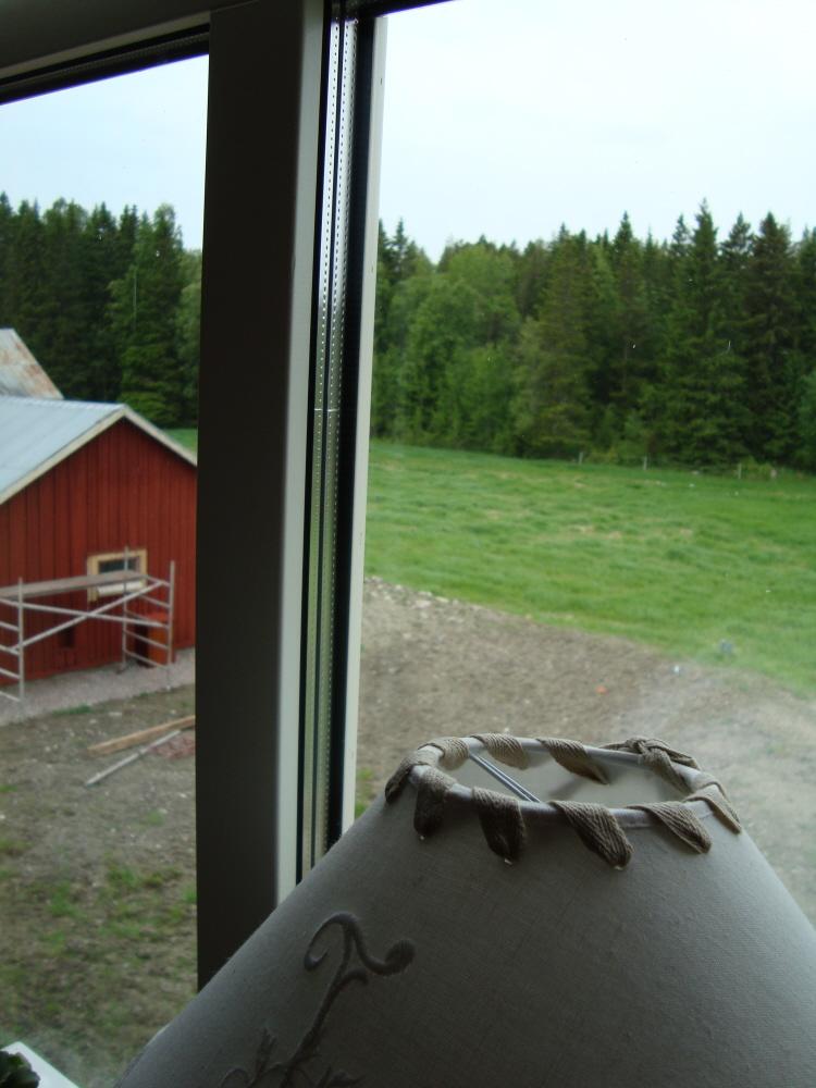 Utsikt från vårt sovrum. Skog, åker och vårt stall som vi börjat måla.